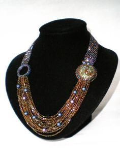 Love this idea for using multiple strands connected by encrusted beadworked cabochons.
