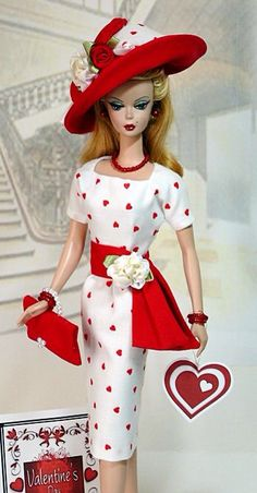 Ensemble Includes the Following Items:  Cotton Heart Print Sheath Red Embellished Sash Belt Embellished Sun Hat Matching HandBag Red Pearl Earrings Red Beaded Necklace & 2 Bracelets Red High Heel Shoes Valentine Hang Tag Free-standing Art Poster Certificate of Authenticity