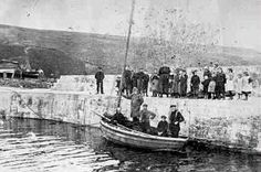 Photograph of a small skiff and crew at Sandend Harbour, Banffshire, Scotland around 1910.