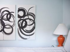 An abstract diptych in black and white on canvas adds a dose of graphic pattern to muted and serene bedroom.