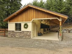 Open breezeway barn with board and batten gable ends, stone wainscot wrap and powder-coated stall fronts