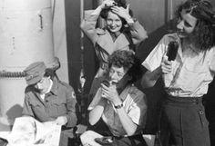 Red Cross members taken onboard a ship during WWII. The lady applying lipstick is Elizabeth Black ~