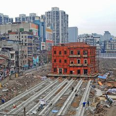Workers prepare for the monolithic movement of a historic site in Changdi Street, Wuhan, Hubei Province, China on March 9th 2016. The historical site was used as a voluntary fire headquarters in the early Republic of China. The building will move 90 metres to the east on concrete rails so that the original location can be redeveloped. Credit: Getty Images/ ChinaFotoPress #fireheadquarters #historicsite #Wuhan #China