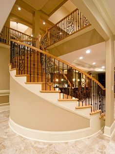 Circular staircase in the lower level of the Heatherstone, plan 5016 www.dongardner.com - This home offers outdoor living areas for every season, including two screened porches with fireplaces, spacious verandas and a custom spa. Inside, decorative ceilings mingle with circular staircases and columns to complete an intricate interior. #Circular #Staircase #Walkout