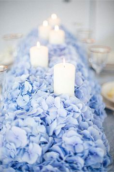 Pale blue hydrangeas create a lush bed for placing a row of candles.