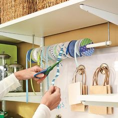Quick Fix. To keep the ribbon neat and easy to access, just put a wooden dowel through the holes in the ribbon spools. Then you can hang the dowel on hooks that are on a shelf, a wall, or wherever you need them.