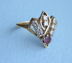 For offer is a vintage one of a kind custom made ring of solid 14K yellow gold (tested but hallmark not visible) set with 8 full brilliant cut diamonds totaling between 1/4th to 1/3rd of a carat or .25 - .30 points, anchored by one round medium red pink semi translucent natural ruby, 6 prong, claw set. The natural ruby is estimated at .18 - .20 carats. The diamonds are judged with 10X magnification and estimated to be well matched at SI1 clarity average. Ring weighs around 3.3 grams...