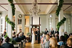 An elegant indoor ceremony with wrapped greenery and crystal chandelier. Photo by Shannen Natasha of The Wedding Artist Collective