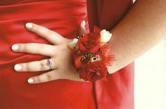 Wrist corsage featuring red roses and white freesia.