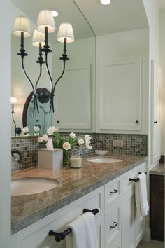 Greyish beige marble counter on white cabinets; glass tile backsplash from Aston Design blog