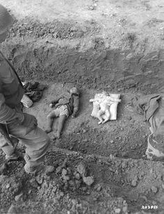 Mauthausen, Austria, An American soldier looking at corpses of children in a mass grave, after the liberation.