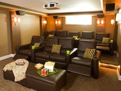 A home theater designed by Shane Inman features large automatic leather recliner chairs, digital projector with surround sound, and attractive wall sconces.