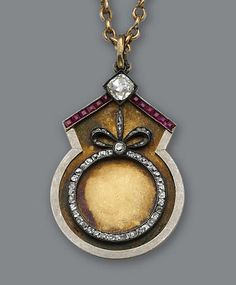 A diamond and ruby pendant and chain, Fabergé, circa 1899, centering an old European-cut diamond accented by calibré-cut rubies, atop a gold panel with single-cut diamonds in a circle and bow motif.