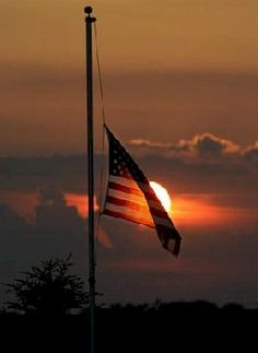 The American Flag at half-mast in the sunset.
