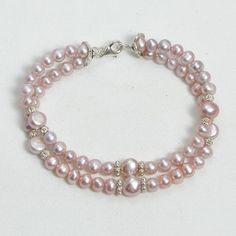 """Handmade gemstone pearl bracelet features 2 strands of semi-precious mauve pearl gemstones, sterling silver accent beads, lobster claw clasp and wire band. 8"""" in length. Add a necklace, pendant and ea"""