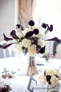 deep eggplant Calla Lilies ivory Roses, purple Ranunculus, Heather accents of Silver Queen in an Art Deco mercury glass vase.
