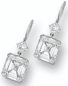 PAIR OF DIAMOND PENDENT EARRINGS.        Each suspending on an emerald-cut diamond weighing 5.36 and 5.05 carats, surmounted by a cushion-shaped diamond, mounted in platinum. Sotheby's.