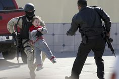 Random act of heroism.  Soldier carries a child from the site of a gun battle.