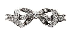 A diamond set bow brooch, circa 1900, set in silver on gold, knotted form.