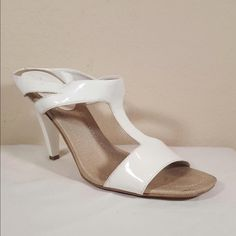 """Nine West sandal! White faux patent leather t-strap heeled mule sandal, by Nine West! They have been worn a handful of times and well loved. Any signs of wear are visible in photos, and I can send more photos upon request. These shoes still look fabulous and have a lot of years left in them! Size 7 with a 3.75"""" heel. No trades! Nine West Shoes Sandals"""
