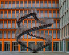 "Umschreibung, Munich, Germany.  This beautifully constructed staircase carries a height of approximately thirty feet. It's double-helix structure keeps visitors coming back. The backdrop is an orange vertical office tower mostly made of glass. This staircase does not lead anywhere and not open for the public to climb, but don't let silly things like ""The Law"" slow you down."