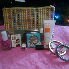 A beauty bundle A ipsy bag , lather ultra light face lotion , natural coconut eye shadow by pacifica , a mirror/card holder,   a gold lia Sophia bracelet , a lia Sophia silver bracelet , a star looks lip gloss, a Julie nail polish, a perfume, a nude eye-shadow by the balm, and a silver ring by lia sophia birchbox Other
