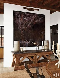 A painting by Pat Steir hangs above the dining area's vintage Belgian console table.