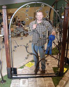 """Elijah Burnett, of Burnett Forge, shows off his award-winning gate, titled """"Forever Blossom."""""""