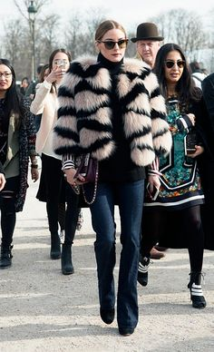 Olivia Palermo wears a turtleneck sweater, Elie Saab fur bolero, flared jeans, black heels, square sunglasses, and a flap bag