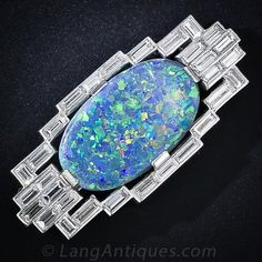 A glorious glowing black opal, displaying an entrancing palette of colors with the emphasis on blue, green and yellow, is elegantly presented in a geometric platinum frame containing thirty straight baguette diamonds totaling 4.00 carats. The surface of the opal displays mild crazing or checking. This unique and majestic Art Deco brooch measures 1 3/4 inches by 13/16 inch.