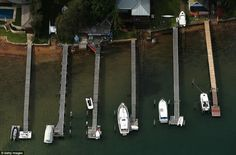 A collection of boats ranging in size are pictured moored at private jetties in Pittwater