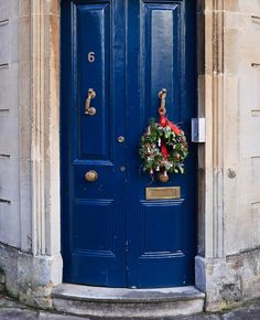 We're charmed by this casual-but-bedecked #wreath in Bristol, England—#ornaments and bow included.