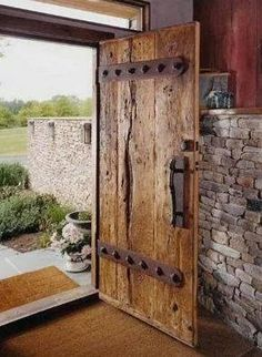 Two inch thick oak barn threshing floor boards and custom hand forged hardware become stout front entrance door. Original red barn siding reused as interior wall treatment. Love thick wooden doors and stone! Cool Doors, The Doors, Panel Doors, Front Door Entrance, Front Entrances, Entry Doors, Sliding Doors, House Entrance, Doorway