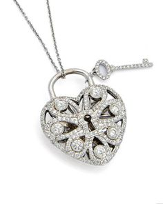 A Diamond 'Filigree Heart with Key' Pendant Necklace, Tiffany & Co. From the Tiffany Locks collection, the filigree bombé heart decorated with round diamonds, accompanied by a diamond-set key, from a fine trace-linking chain, mounted in 18k white gold, length 17 1/2 ins, signed T & Co., with original box