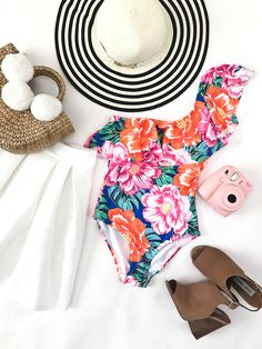 floral one shoulder one piece swimsuit, white pleated scuba skirt, striped floppy hat, straw pom pom basket bag, pink instax mini camera