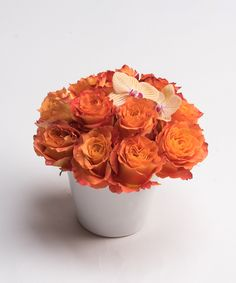 Summer Charm A lovely collection of orange Free Spirit Roses with an accent of Kaleidoscope Phalaenopsis Orchid blooms is designed in a decorative white ceramic container.