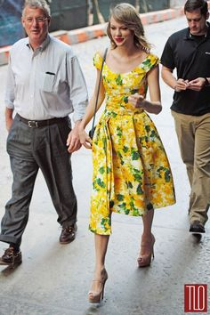 Taylor Swift out with her brother and father in New York City in an Oscar de la Renta floral pleated dress paired with Prada shoes.