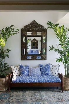 Fab blue print sofa with mixed print, layers of cushions; distressed kilim rug and Indonesian(?) style mirror