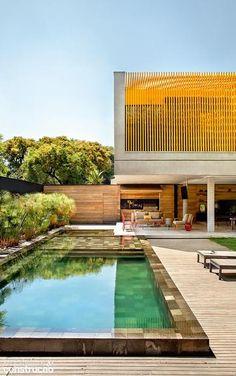 O brise metálico amarelo-ovo preserva a intimidade dos moradores e dá forte identidade à casa de vidro e concreto paulistana
