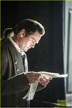 "Screenshot of Henry Thomas as John Adams in ""Sons of Liberty"" - ""He's taken to reading the broadsheets every day."" ""I would, too - how else would we know what's going on in the outside world?"" ""True. But I worry for him sometimes. Lately, whatever it is he's reading, it just makes him angry. And then he storms out with the paper in his hand, and I know he goes to the tavern after that."""