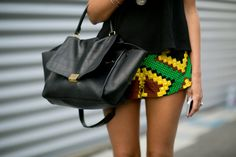 The Accessory Stars of Paris Fashion Week: A clutch that doubles as a work of art.  : The perfect complement to any Fashion Week look? Chanel, of course.  : A novel clutch pops against her grays.  : A bold blue to play off a great print.  : An ultraluxe Céline tote paired up nicely with high-impact shorts.