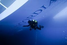 Italian police diver inspects the hull of the partially submerged Costa Concordia