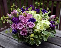 A wonderful table centerpiece with lime hydrangea, purple blooms of roses, tulips, lisianthus and stock, and green fillers including buplerum and pittosporum.