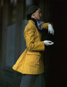 Woman wearing yellow coat, scarf, hat, white gloves and skirt, photographed by Frances McLaughlin-Gill for Vogue, 1947