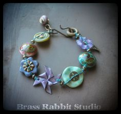 """Mixed media, cuff style bracelet with artisan Lampwork by Genea, SueBeads, enameled pinwheel by Jade Scott, ceramic flower by Bo Hulley Beads, ceramic disk by Pajego Art House, and lucite flower with brass leaf charm, bracelet has a Lampwork ring by Leah Deeb and hook clasp closure with a Lampwork bead charm (bead by CatLampwork) fits a 7"""" wrist perfect."""