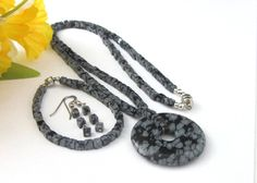 """Snowflake Obsidian Gemstone Donut Pendant Necklace - by Thesingingbeader -- """"Snowflake obsidian is a lovely gemstone resembling snowflake patterns. In this handmade jewelry set, the snowflakes are a light gray color, the background black. The set includes a long donut style pendant necklace, a bracelet, and dangling earrings."""""""