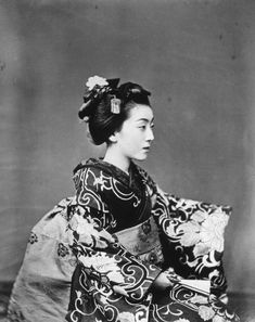 A beautiful Japanese geisha poses for a side profile shot in this striking portrait, taken by Felice Beato circa 1865.