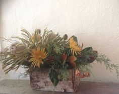 Winter in the desert centerpiece with magnolia, cedar, proteas, chrysanthemums and eucalyptus pods in a birch box.