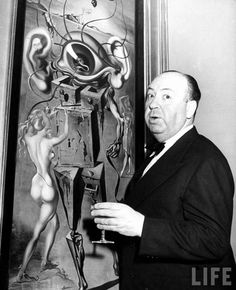 Alfred Hitchcock in 1944 admiring a painting by Salvador Dalí very appropriately titled 'Movies'.
