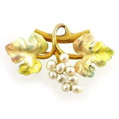 A gold, enamel and pearl brooch, c.1890, in the form of a bunch of grapes and vine leaf, symbols of intoxication, hospitality and plenty. (Bentley & Skinner)